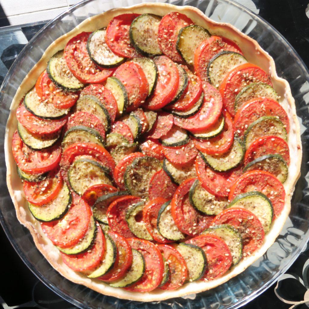 Disposer ensuite les rondelles de courgettes et de tomates en les alternant. Saupoudrer de zaatar ou de sel et d'herbes et enfourner pour 20 minutes à 180°C.